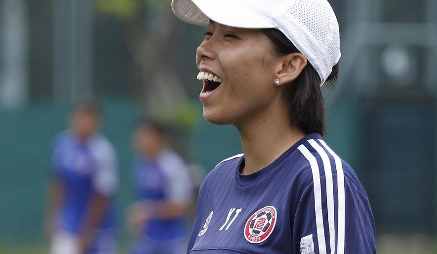 FILE - In this May 6, 2016 file photo, Hong Kong's Eastern Sports Club head coach Chan Yuen-ting laughs during a training session in Hong Kong. World Cup winning coach Luiz Felipe Scolari's first task in trying to take Guangzhou Evergrande to a third Asian Champions League will be to face a team coached by a 28 year-old woman. The draw has pitted the Chinese powerhouse against Hong Kong club Eastern F.C., whose coach Chan became the first woman to lead a men's team to a title in a professional top flight league when Eastern won the 2016 Hong Kong Premier League. (AP Photo/Kin Cheung, File)