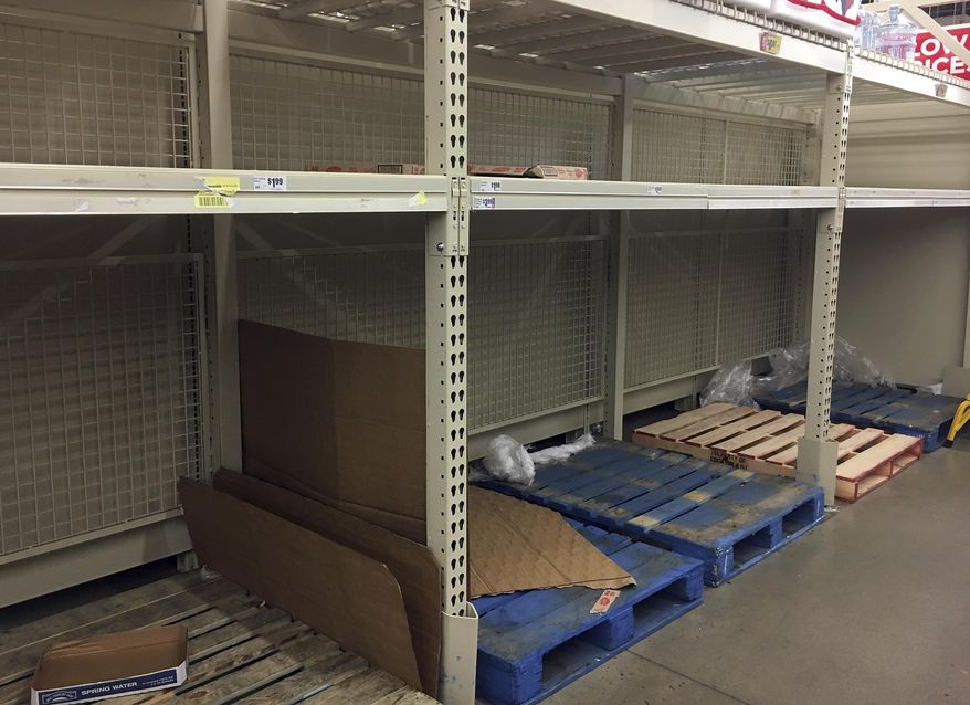 In this Thursday, Dec. 15, 2016 photo, empty shelves are left after residents rushed to H-E-B to buy water after a recent back-flow incident in the industrial district according to a city news release, in Corpus Christi, Texas. (Gabe Hernandez/Corpus Christi Caller-Times via AP)
