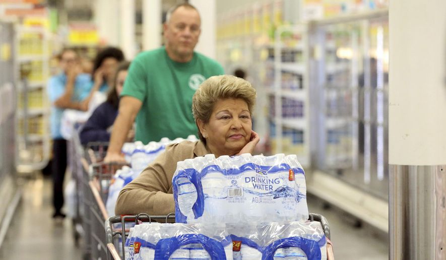 Customers stand in line to pay for cases of water at an H-E-B store Thursday, Dec. 15, 2016, in Corpus Christi, Texas. The city is warning its 320,000 residents not to use tap water because it might be contaminated with petroleum-based chemicals, prompting a rush on bottled water and the closure of local schools. (Gabe Hernandez/Corpus Christi Caller-Times via AP)