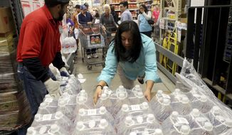 H-E-B employees remove bottles of water from a crate to hand out to customers Thursday morning, Dec. 15, 2016, in Corpus Christi, Texas. The city is warning its 320,000 residents not to use tap water because it might be contaminated with petroleum-based chemicals, prompting a rush on bottled water and the closure of local schools. (Gabe Hernandez/Corpus Christi Caller-Times via AP)