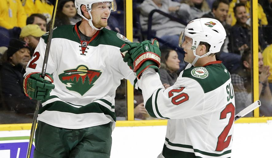 Minnesota Wild center Eric Staal (12) celebrates with Ryan Suter (20) after Staal scored a goal against the Nashville Predators during the first period of an NHL hockey game Thursday, Dec. 15, 2016, in Nashville, Tenn. (AP Photo/Mark Humphrey)