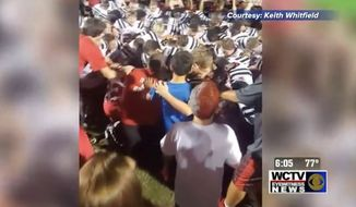 Eddie Metcalf, a football coach at Wakulla Middle School in Wakulla County, Florida, has been reprimanded by the school district after he was captured on video taking a knee during a player's pre-game prayer. (WCTV)
