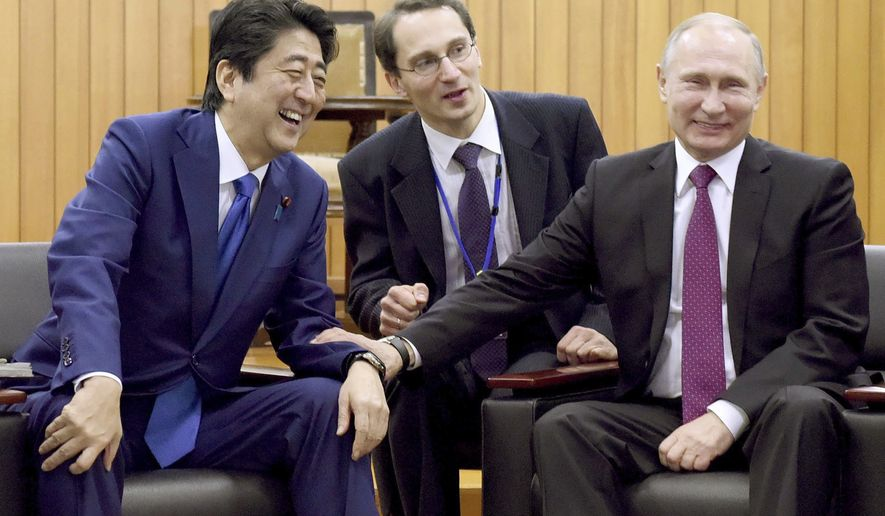 Russian President Vladimir Putin, right, chats with Japanese Prime Minister Shinzo Abe, left, during their visit to the Kodokan Judo Institute, the headquarters of the worldwide judo community, in Tokyo, Friday, Dec. 16, 2016. Russia and Japan agreed Friday to hold talks on joint economic development on four islands at the center of a territorial dispute between the countries. (Toru Yamanaka/Pool Photo via AP)