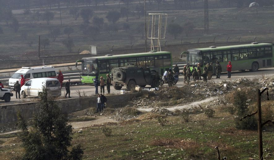 In this photo released by the Syrian official news agency SANA, green government buses carry residents evacuating from eastern Aleppo, Syria, Friday, Dec. 16, 2016. The Syrian government suspended evacuations from eastern Aleppo just hours after they resumed on Friday, saying that rebels had opened fire on a convoy of evacuees at a crossing point with the enclave, state TV reported. (SANA via AP)