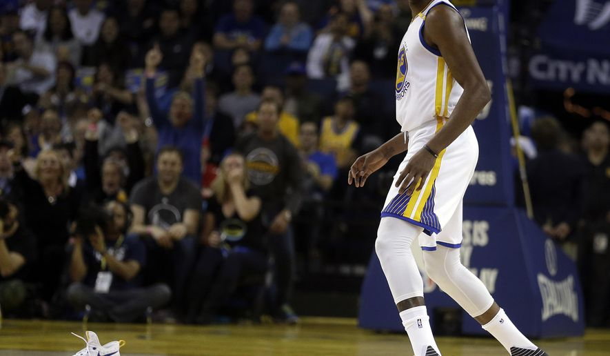 Golden State Warriors' Kevin Durant walks towards his shoe after it came off during the first half of play in an NBA basketball game against the New York Knicks Thursday, Dec. 15, 2016, in Oakland, Calif. (AP Photo/Ben Margot)