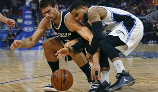 Brooklyn Nets center Brook Lopez, left, and Orlando Magic guard D.J. Augustin battle for the ball during the first half of an NBA basketball game in Orlando, Fla., on Friday, Dec. 16, 2016. (AP Photo/Reinhold Matay)
