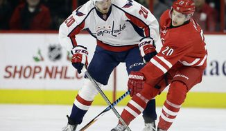 Carolina Hurricanes' Sebastian Aho (20), of Finland, and Washington Capitals' Lars Eller (20), of Denmark, chase the puck during the first period of an NHL hockey game in Raleigh, N.C., Friday, Dec. 16, 2016. (AP Photo/Gerry Broome)