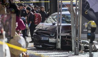 Bystanders look on at the site of a crash at a Chinatown bus stop Friday, Dec. 16, 2016, in San Francisco. Authorities say multiple people have been injured after a car plowed into the bus stop. (Jessica Christian  /The San Francisco Examiner via AP)