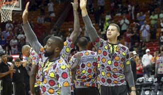 Los Angeles Clippers forward Blake Griffin, right, high-fives teammates before an NBA basketball game against the Miami Heat, Friday, Dec. 16, 2016, in Miami. The Clippers were wearing jerseys to honor former TNT reporter Craig Sager who died Thursday. (AP Photo/Lynne Sladky)