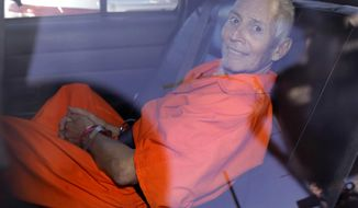 FILE - In March 17, 2015, file photo, New York real estate heir Robert Durst smiles as he is transported from Orleans Parish Criminal District Court to the Orleans Parish Prison after his arraignment on murder charges in New Orleans. Durst, 73, charged with murdering a friend in Los Angeles told a prosecutor he never fled because of inertia. Documents released Friday, Dec. 16, 2016, show Durst told a prosecutor he was the world's worst fugitive. Durst did not confess to the killing but he said he was willing to provide information Deputy District Attorney John Lewin sought in exchange for a better prison assignment.  (AP Photo/Gerald Herbert, File)