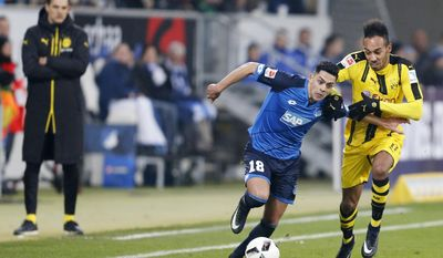 Hoffenheim's Nadiem Amiri, left, and Dortmund's Pierre-Emerick Aubameyang challenge for the ball while Dortmund's coach Thomas Tuchel, very left, looks on during a German first division Bundesliga soccer match between TSG 1899 Hoffenheim and Borussia Dortmund in Sinsheim, Germany, Friday, Dec. 16, 2016.(AP Photo/Michael Probst)