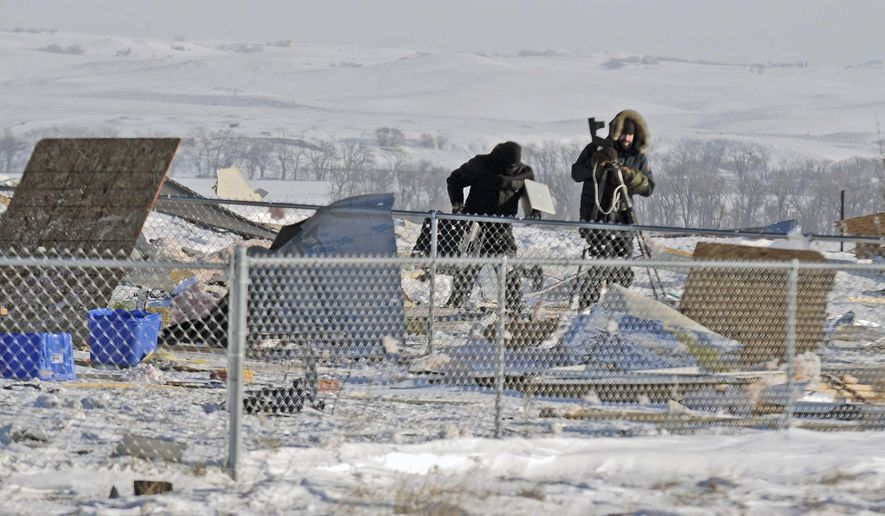 Two technicians from the North Dakota Bureau of Criminal Investigation investigate the scene of an explosion north of the city of Mandan, N.D., that killed two people and injured a young woman shortly after midnight on Wednesday, Dec. 14, 2016. The explosion left the house unrecognizable and did not cause a fire. Several people from the North Dakota Bureau of Criminal Investigation (BCI) were at the scene on Wednesday morning. (Tm Strommer/The Bismarck Tribune via AP)