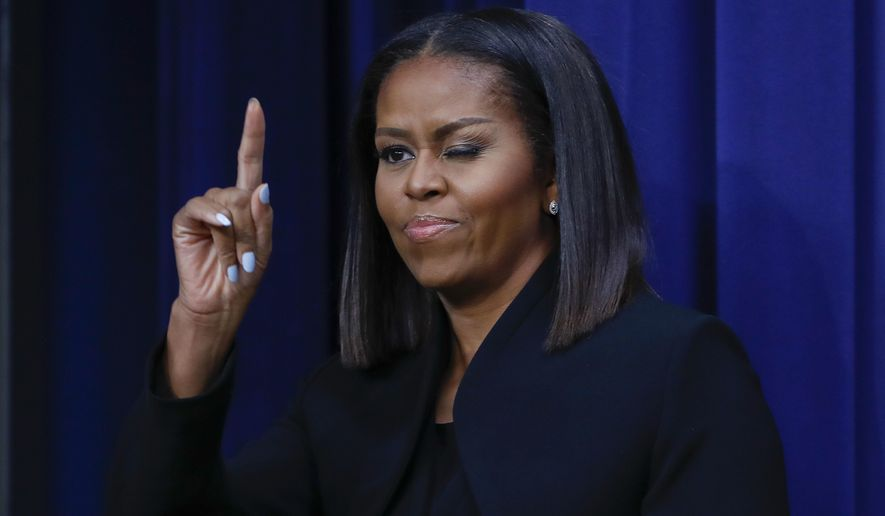 First lady Michelle Obama 'winks' and gestures to guests after after speaking following the screening for the movie 'Hidden Figures,' Thursday, Dec. 15, 2016, in the South Court Auditorium in the Eisenhower Executive Office Building on the White House complex in Washington. (AP Photo/Pablo Martinez Monsivais)