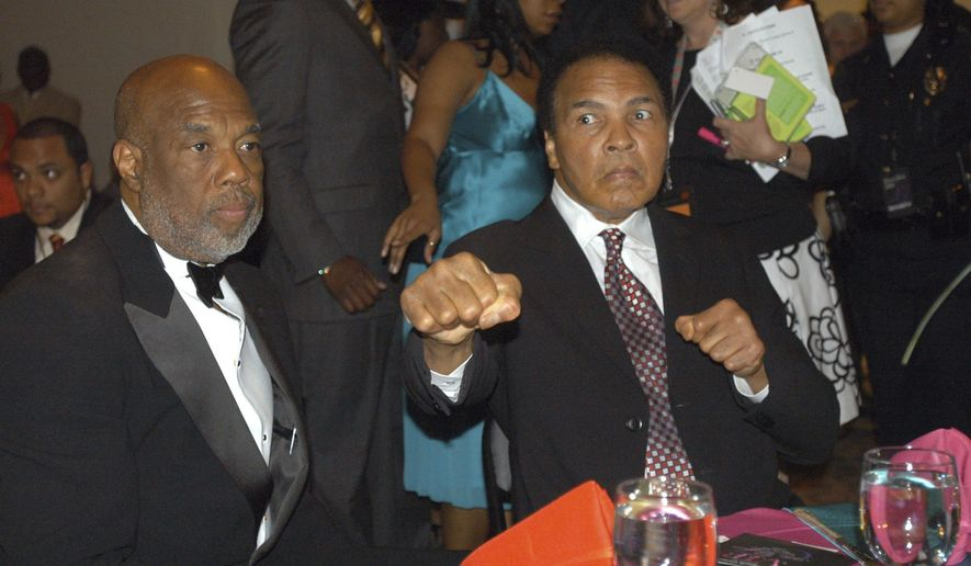 FILE - In this May 5, 2006 file photo, photographer Howard Bingham, left, and longtime friend Muhammad Ali attend a reception at the Muhammad Ali Center in Louisville, Ky. Bingham, the longtime personal photographer, confidant and close friend of Ali, died Thursday, Dec. 15, 2016, at age 77.  (AP Photo/Brian Bohannon, File)