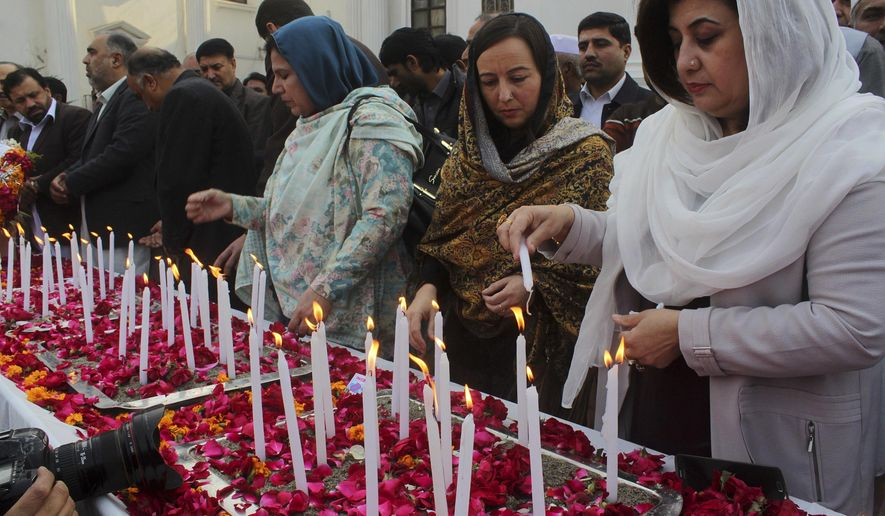 Pakistani lawmakers from the provincial Khyber Pakhtunkhwa assembly light candle during a ceremony to mark second anniversary of the attack on a Peshawar school in 2014, in Peshawar, Pakistan, Friday, Dec. 16, 2016. Pakistani Taliban militants attacked an army-run school in Peshawar, killing more than 150 people, mostly children, on Dec. 16. 2014. (AP Photo/Muhammad Sajjad)