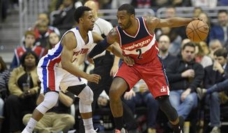 Washington Wizards guard John Wall (2) dribbles against Detroit Pistons guard Ish Smith (14) during the first half of an NBA basketball game, Friday, Dec. 16, 2016, in Washington. (AP Photo/Nick Wass)