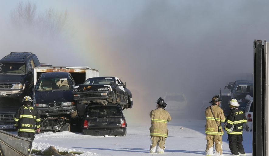 Firefighters stand in foam and look on as a rainbow appears at an auto-wrecking yard fire Friday, Dec. 16, 2016, in Richmond, Calif. About 40 cars were destroyed in the massive fire early Friday, officials said. Dark plumes of smoke could be seen wafting across the East Bay and in San Francisco as firefighters worked to control the blaze. (AP Photo/Eric Risberg)