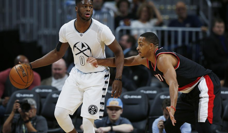 Denver Nuggets guard Emmanuel Mudiay, left, looks to pass the ball as Portland Trail Blazers guard C.J. McCollum defends in the first half of an NBA basketball game Thursday, Dec. 15, 2016, in Denver. (AP Photo/David Zalubowski)