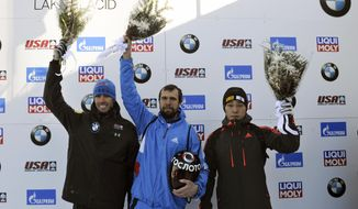 Winner Alexander Tretiakov, of Russia, center, celebrates with second placed Matthew Antoine, of the United States, left, and third placed Sungbin Yun, of South Korea, after the men's skeleton World Cup race on Friday, Dec. 16, 2016, in Lake Placid, N.Y. (AP Photo/Hans Pennink)
