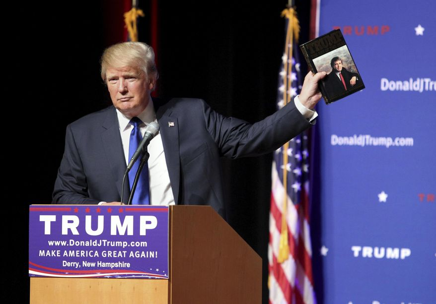 """FILE - In this Aug. 19, 2015 file photo, Republican presidential candidate Donald Trump holds up a copy of his 1987 book, """"Trump: The Art of the Deal"""" during his campaign town hall event at Pinkerton Academy in Derry, N.H. Trump's first book is a memoir/manifesto dedicated to a life of big-time negotiating.  (AP Photo/Mary Schwalm, File)"""