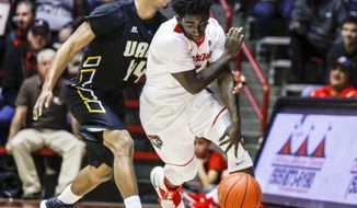 Arkansas Pine Bluff's Ghiavonni Robinson (44) attempts to make a steal on New Mexico's Jordan Hunter (3) during the first half of an NCAA college basketball game in Albuquerque, N.M., Saturday, Dec. 17, 2016. (AP Photo/Juan Antonio Labreche)