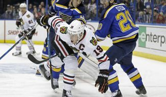 Chicago Blackhawks' Jonathan Toews (19) tries to get past St. Louis Blues' Alexander Steen (20) and Jay Bouwmeester (19) in the first period of an NHL hockey game, Saturday, Dec. 17, 2016 in St. Louis. (AP Photo/Tom Gannam)