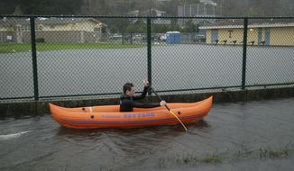 FILE - In this Dec. 15, 2016, file photo, Julian LePelch paddles his kayak past a flooded field at Tamalpais High School in Mill Valley, Calif. California's first winter storm of 2017 will shed welcome rain over the rivers, pumps and pipes that move California's water from north to south, and may open a new era of tensions over where that water goes, under a new federal law dictating that the state's farmers get the biggest possible share. (AP Photo/Eric Risberg, File)