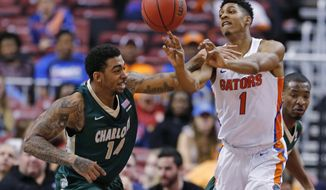 Florida forward Devin Robinson (1) passes under pressure from Charlotte forward JC Washington (14) during the first half of an NCAA college basketball game in the Orange Bowl Classic tournament, Saturday, Dec. 17, 2016, in Sunrise, Fla. (AP Photo/Joe Skipper)