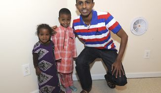 In this Dec. 8, 2016 photo, Somali refugees, Ibrahim Hassan, right, with his children, daughter, Hafsa Ibrahim Ahmed, 2, left, and son, Hamza Ibrahim Ahmed, 4, middle, pose at their apartment in Owensboro, Ky. The family, including his wife Sahara Nekow, moved here two months ago from a refugee camp in northeast Kenya. He had moved from his native Somalia to that camp with his father and grandmother in 1994 and his wife, also Somali, moved there with her parents since 1992.(Alan Warren/The Messenger-Inquirer via AP)
