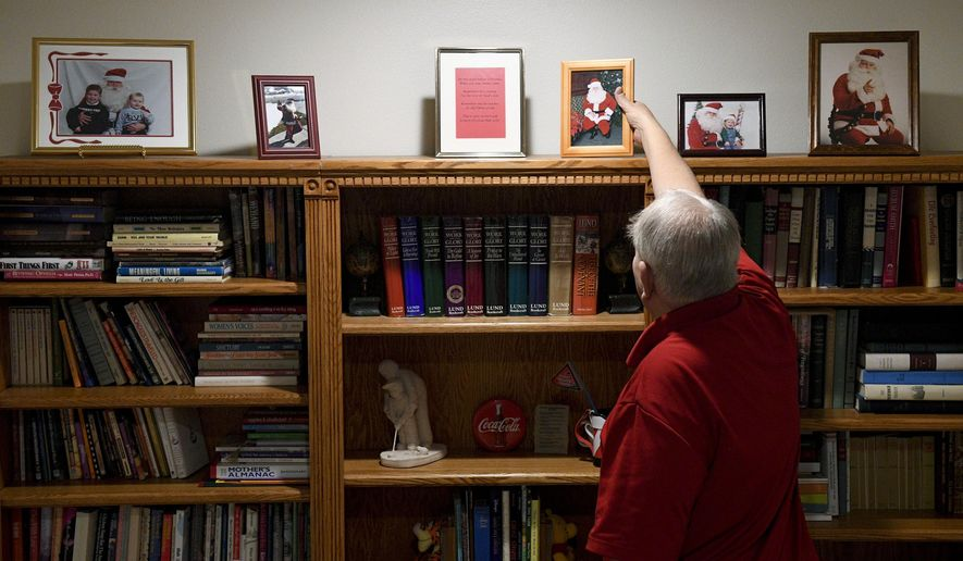 ADVANCE FOR WEEKEND EDITIONS, DEC. 17-18 - In this Friday, Dec. 9, 2016 photo, Tom Carter puts pictures of himself dressed as Santa Claus back on a shelf at his home in Orem, Utah. Tom is a part of the second generation of the three generations of Santa Clauses in the Carter family. (Isaac Hale/The Daily Herald via AP)