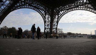 Visitors walk under the Eiffel Tower on the fourth day of the strike, in Paris, Friday, Dec. 16, 2016. The Eiffel Tower, which is normally open every single day of the year, closed Tuesday because of a strike over salaries and working conditions. (AP Photo/Christophe Ena)