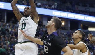 Colorado State forward Kimani Jackson, left, puts the ball in for a basket as Kansas State forward Dean Wade, center, and Colorado State guard Gian Clavell watch during the first half of an NCAA college basketball game Saturday, Dec. 17, 2016, in Denver. (AP Photo/David Zalubowski)