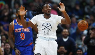 Denver Nuggets forward Kenneth Faried (35) celebrates after dunking a basket over New York Knicks center Kyle O'Quinn in the first half of an NBA basketball game Saturday, Dec. 17, 2016, in Denver. (AP Photo/David Zalubowski)