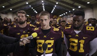 FILE - In this Dec. 15, 2016, file photo, University of Minnesota wide receiver Drew Wolitarsky, flanked by quarterback Mitch Leidner, left, and tight end Duke Anyanwu stands in front of other team members as he reads a statement on behalf of the players in the Nagurski Football Complex in Minneapolis, Minn. The University of Minnesota football team will play in the Holiday Bowl, reversing a threat to boycott the game because of the suspension of 10 players accused of sexual assault. The players made the announcement at a news conference Saturday, Dec. 17, after a group of seniors from the team met with the board of regents, university President Eric Kaler and athletic director Mark Coyle on Friday night. (Jeff Wheeler/Star Tribune via AP, File)