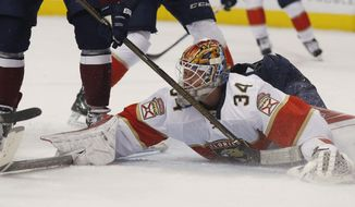 Florida Panthers goalie James Reimer falls on the ice to stop a shot against the Colorado Avalanche in the third period of an NHL hockey game Friday, Dec. 16, 2016, in Denver. The Panthers won 3-1. (AP Photo/David Zalubowski)