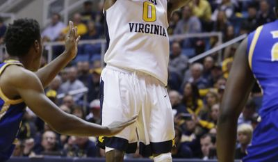 West Virginia guard Teyvon Myers (0) takes a shot while being defended by UMKC guard Isaiah Ross (2) during the first half of an NCAA college basketball game, Saturday, Dec. 17, 2016, in Morgantown, W.Va. (AP Photo/Raymond Thompson)