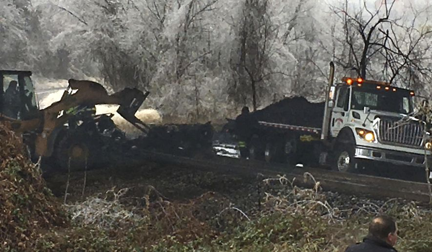 Authorities clean up the remains of a tanker truck the slid off Interstate 95 in Baltimore, Md., on Saturday morning, Dec. 17, 2016, following an overnight ice storm. (Karl Merton Ferron/The Baltimore Sun via AP)