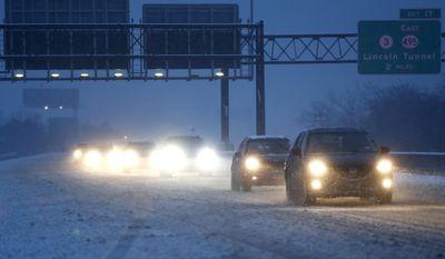 Vehicles commute under snowfall northbound on the New Jersey Turnpike, Saturday, Dec. 17, 2016, in Ridgefield, N.J. (AP Photo/Julio Cortez)