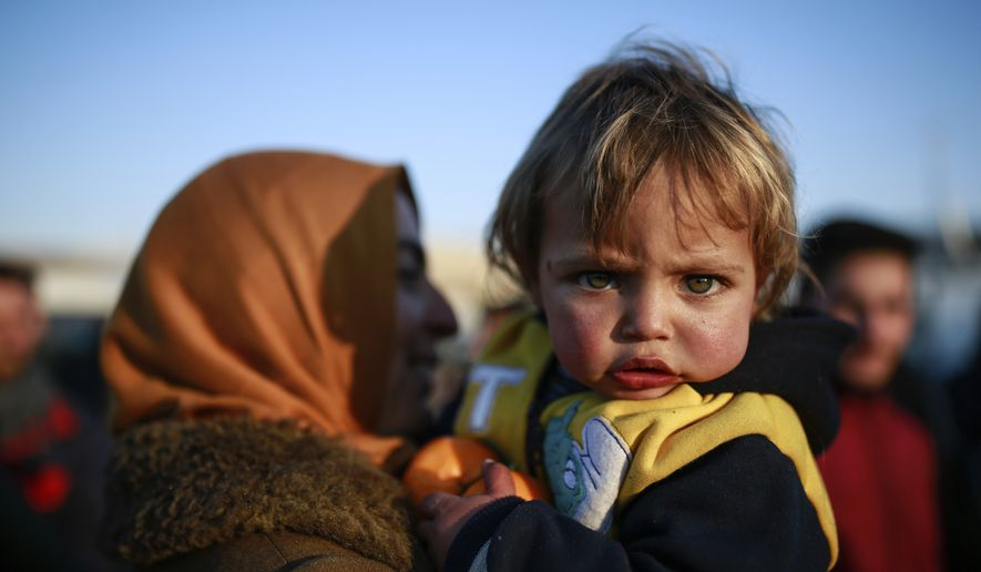 Ritach Halif, 2, is carried by her mother, after the family which came from Idlib, Syria, crossed into Turkey at the Cilvegozu border gate with Syria, near Hatay, southeastern Turkey, Sunday, Dec, 18, 2016. Several people were able to cross into Turkey after they managed to leave the embattled Syrian city during the ceasefire, and arrived in Turkey by their own means. The Aleppo evacuation was suspended Friday after a report of shooting at a crossing point into the enclave by both sides of the conflict. (AP Photo/Emrah Gurel)