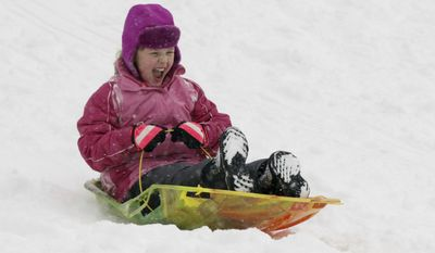Olivia DePew, 7, screams with delight as she sleds down Ravine Park hill in the snow Saturday, Dec. 17, 2016, in Kohler, Wis. DePew, according to her father Craig, recently moved from Arkansas to Kohler and this is their first Wisconsin Winter. (Gary C. Klein/The Sheboygan Press via AP)