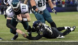 Philadelphia Eagles quarterback Carson Wentz (11) dives into the end zone for a touchdown as Baltimore Ravens strong safety Eric Weddle (32) hangs on during the second half of an NFL football game in Baltimore, Sunday, Dec. 18, 2016. The Ravens defeated the Eagles 27-26. (AP Photo/Gail Burton)