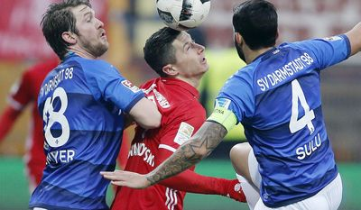 Darmstadt's Jerome Gondorf, left, and Darmstadt's Aytac Sulu, right, frame  Bayern's Robert Lewandowski as they challenge for the ball  during a German first division Bundesliga soccer match between Darmstadt 98 and Bayern Munich in Darmstadt, Germany, Sunday, Dec. 18, 2016.(AP Photo/Michael Probst)
