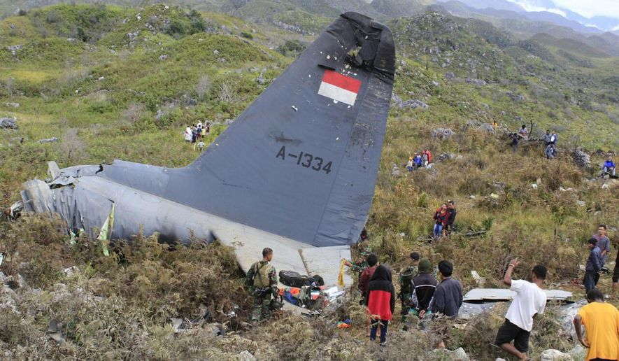 Rescuers collect personal belongings of the victims of an Indonesian Air Force plane that crashed in the mountainous area in Wamena, Papua province, Indonesia Sunday, Dec. 18, 2016. The Hercules C-130 transport plane crashed in bad weather in the easternmost province, killing all people on board. (AP Photo/Gerry Kossay)