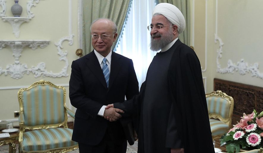 In this photo released by official website of the office of the Iranian Presidency, President Hassan Rouhani, right, and Director General of the International Atomic Energy Agency, IAEA, Yukiya Amano shake hands for media at the start of their meeting at the Presidency office in Tehran, Iran, Sunday, Dec. 18, 2016. (Iranian Presidency Office via AP)