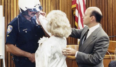 "FILE - In a Sept. 14, 1989 file photo, defense attorney William Graysen, right, positions the hand of Zsa Zsa Gabor on the face of Beverly Hills Police Officer Paul Kramer during a reenactment of the June 14 incident that resulted in Miss Gabor's arrest. Kramer, a motorcycle cop, testified in Beverly Hills, Calif., that Miss Gabor was the motorist who cursed him for stopping her Rolls-Royce, slapped him and screamed ""Do you know who I am?"" Gabor died Sunday, Dec. 18, 2016, of a heart attack at her Bel-Air home, her husband, Prince Frederic von Anhalt, said. She was 99. (AP Photo/LAT, File)"