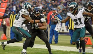 Baltimore Ravens running back Kenneth Dixon (30) carries the ball between Philadelphia Eagles free safety Rodney McLeod (23) and cornerback Jalen Mills (31) for a touchdown during the second half of an NFL football game in Baltimore, Sunday, Dec. 18, 2016. (AP Photo/Nick Wass)