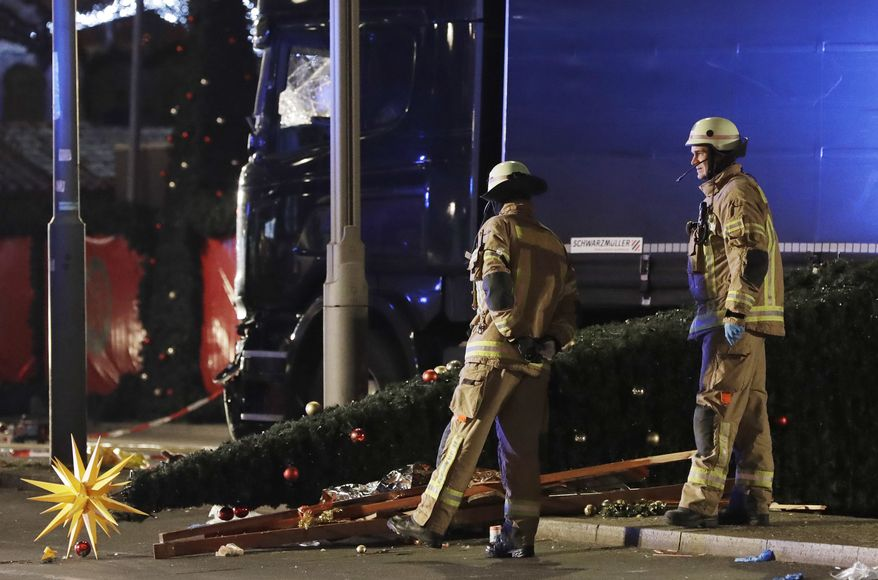 Firefighters look at a toppled Christmas tree after a truck ran into a crowded Christmas market and killed several people in Berlin, Germany, on Monday. (Associated Press)