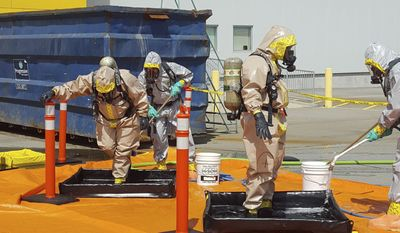 In this June 27, 2016, file photo provided by the Royal Canadian Mounted Police, members of the RCMP go through a decontamination procedure in Vancouver after intercepting a package containing approximately 1 kilogram (2.2 pounds) of the powerful opioid carfentanil imported from China. U.S. assertions that China is the top source of the synthetic opioids that have killed thousands of drug users in the U.S. and Canada are unsubstantiated, Chinese officials told the Associated Press. (Royal Canadian Mounted Police via AP, File)