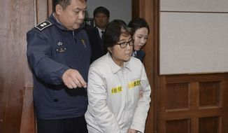 Choi Soon-sil, center, the jailed confidante of disgraced South Korean President Park Geun-hye, appears for the first day of her trial at the Seoul Central District Court in Seoul, South Korea, Monday, Dec. 19, 2016. (Korea Pool via AP)