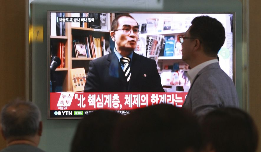 """In this Aug. 17, 2016 photo, people watch a TV news program showing a file image of Thae Yong Ho, a high-profile North Korean defector, at Seoul Railway Station in Seoul, South Korea. Thae told on Monday, Dec. 19, 2016, South Korean lawmakers that he decided to flee because of disillusionment with what he describes as a """"tyrannical reign of terror"""" by leader Kim Jong Un. The letters read """"A high-ranking North Korean diplomat."""" (AP Photo/Ahn Young-joon, File)"""